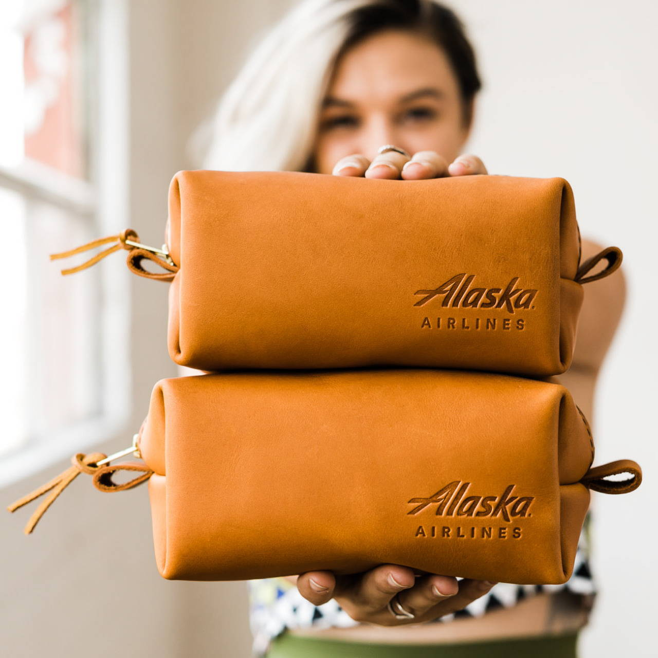 woman holding leather corporate branded dopp kits