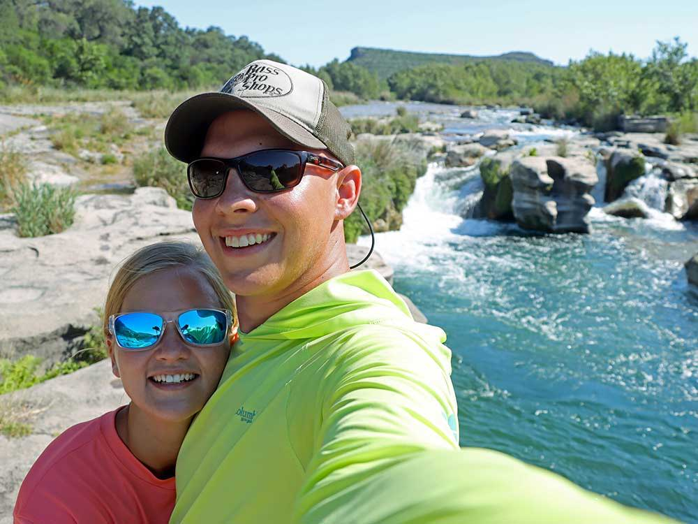 Texas kayak fisher and his wife posing infront of some rapids