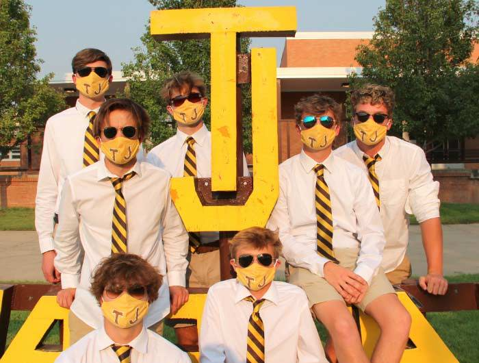 High school seniors wearing striped ties in school colors and matching face masks