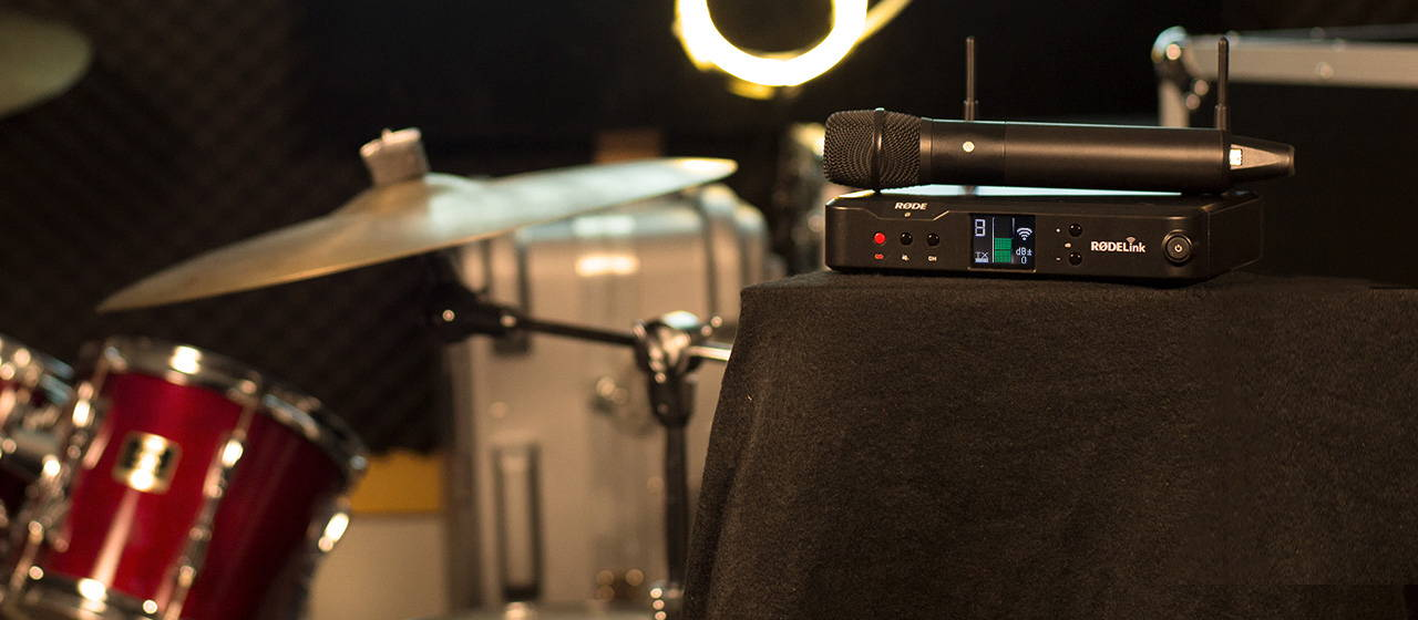 Rode Microphone sits on top of an amplifier with a drum kit in the background
