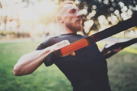 Mann trainiert zu Hause im Garten nach einem Muskelaufbau-Trainingsplan