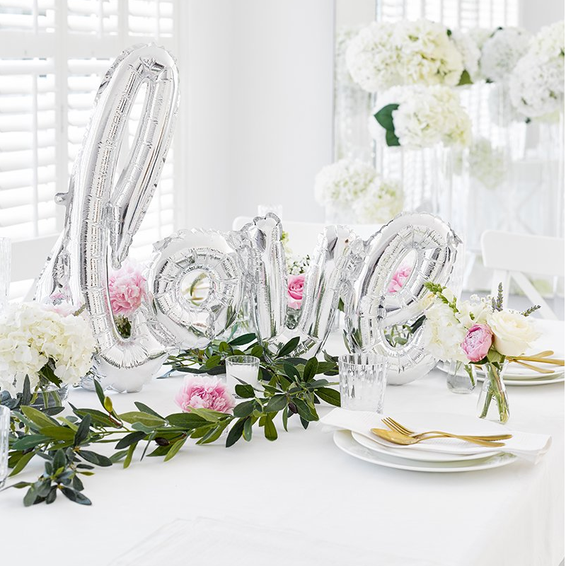 A photo of a table laid out for a modern wedding style with silver foiled 'love' wedding balloon, a flower garland, and tableware in white and gold