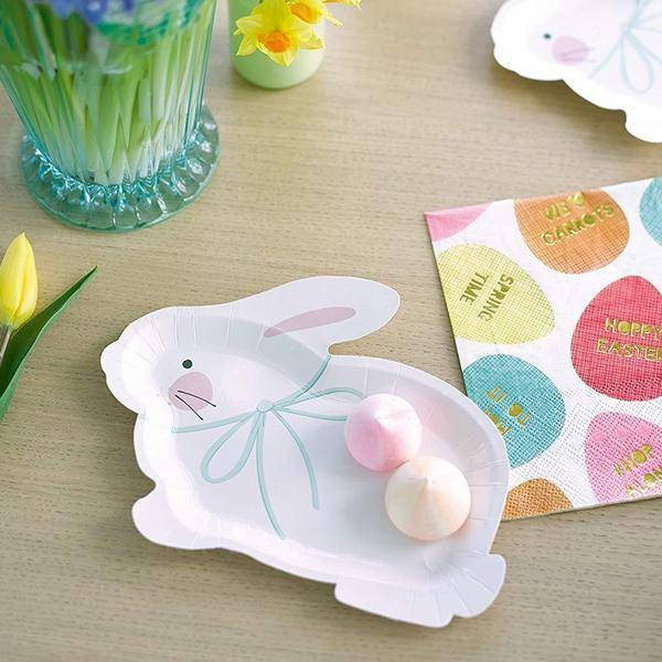 Easter party table decorated with one Springtime Bunny rabbit shaped plate, beside a Springtime Bunny Hop to it napkin and some spring flowers.