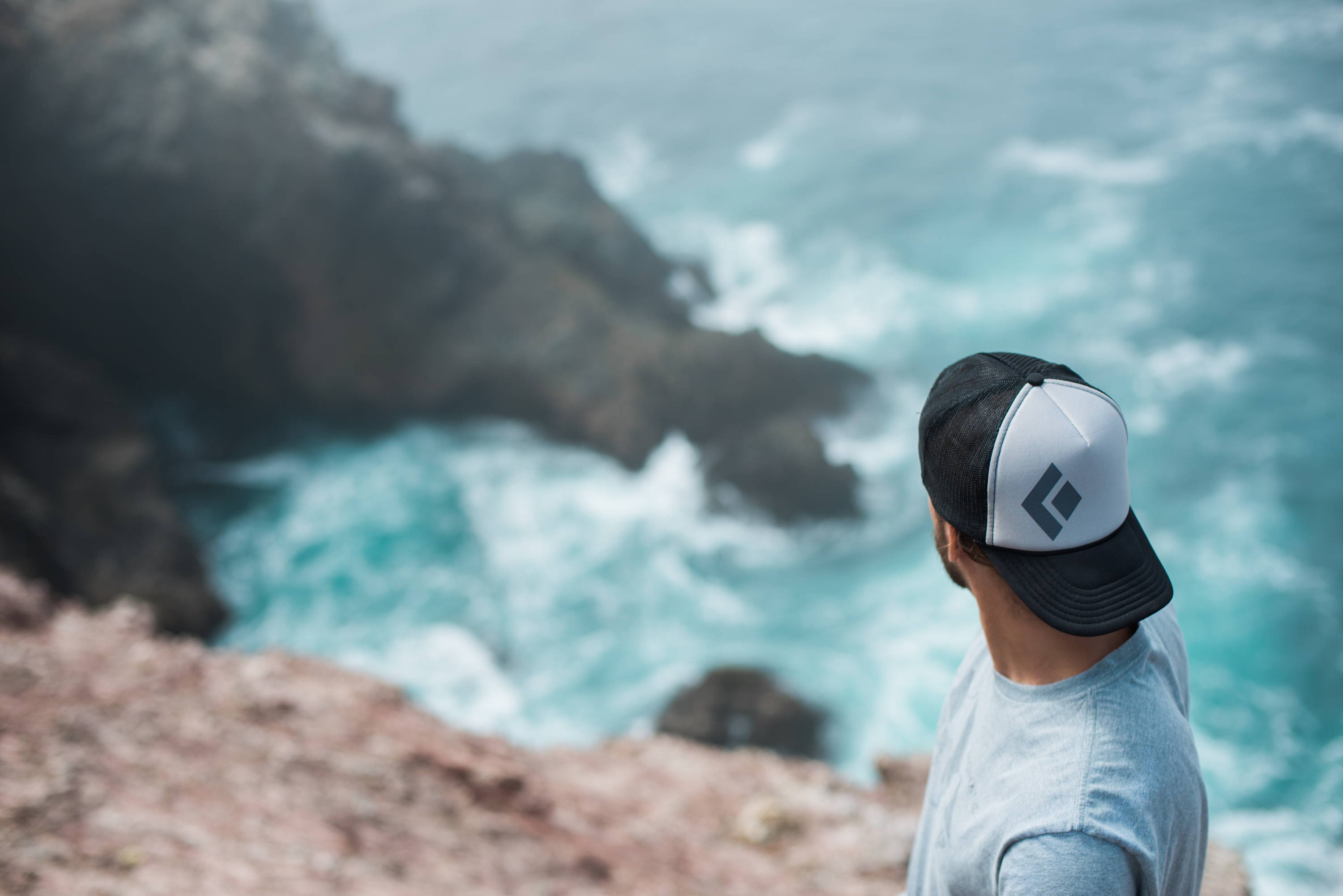 overlooking clear blue ocean backwards hat rocky beach scenery