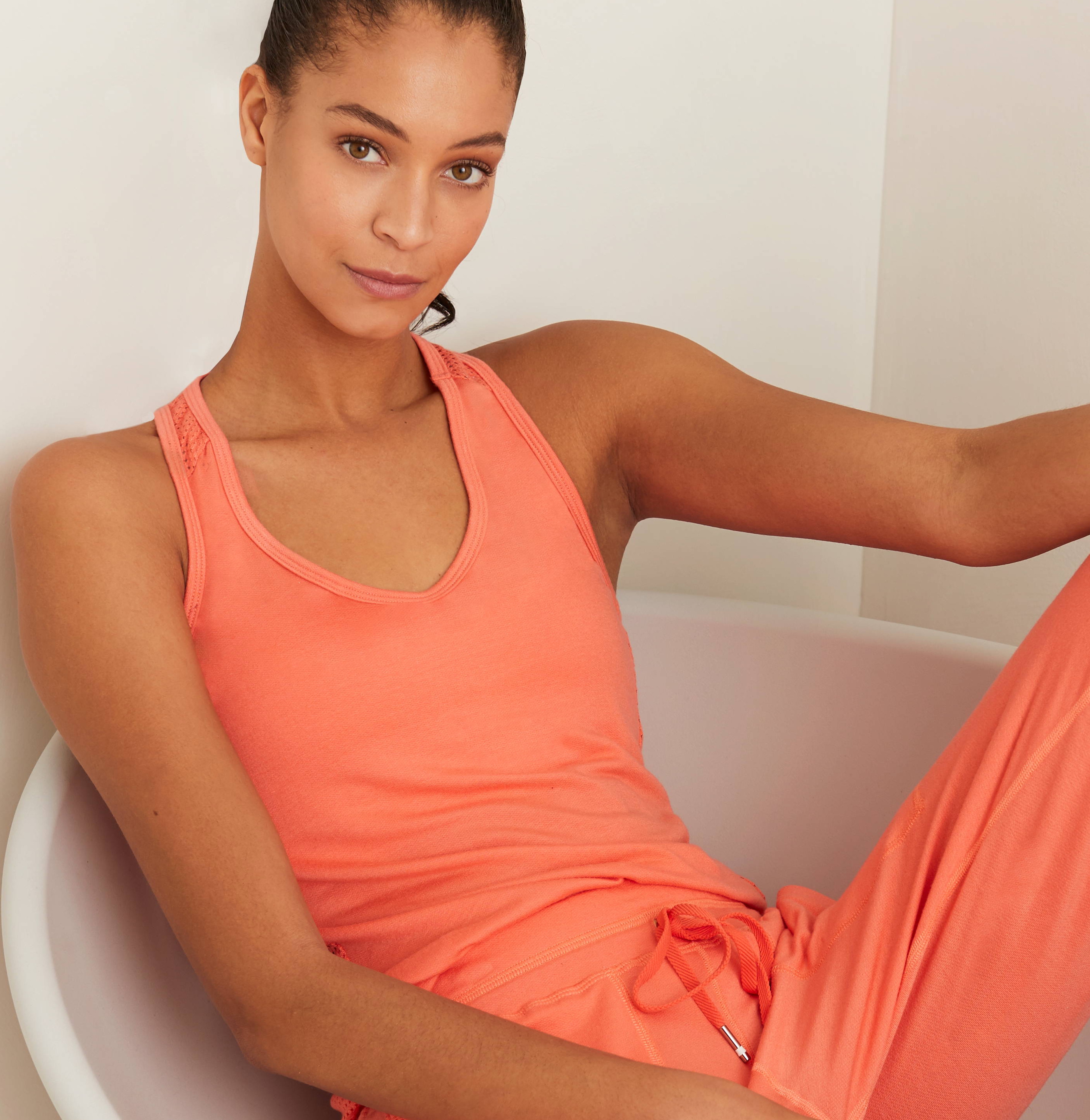Photo featuring a model sitting in a chair in our new Coral Sweat Set.