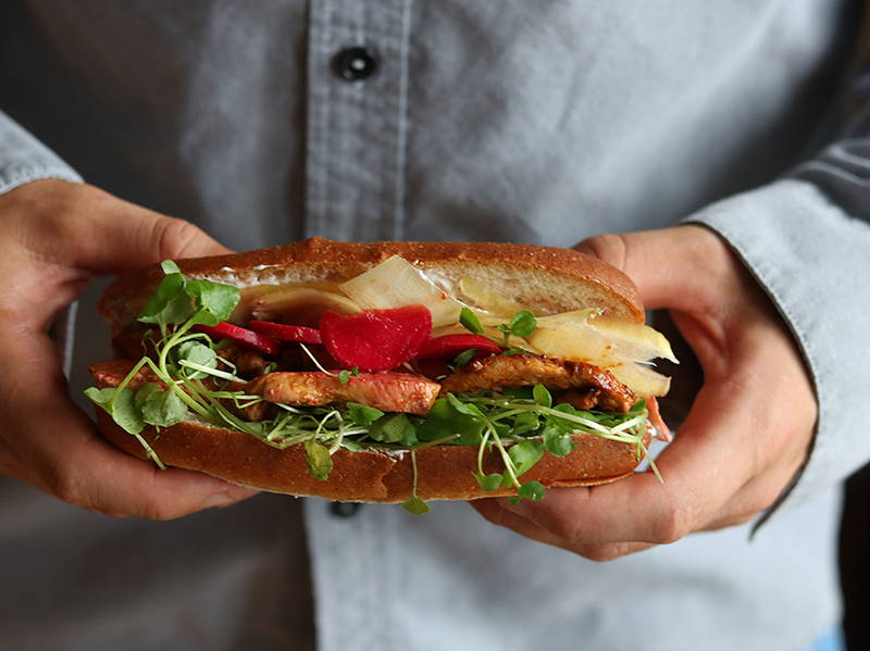 Recette de sandwich banh-mi au poulet sur le blogue de la nutritionniste Isabelle Huot Docteure en nutrition. Ce sandwich original d'inspiration vietnamienne apportera de la diversité à vos lunchs du midi. Cette recette de sandwich santé combine des carottes et des radis marinés, des micro-pousses, de la coriandre, du yogourt grec et du poulet grillé.