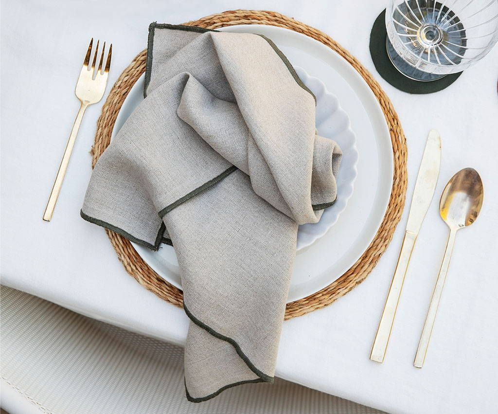Two white plates on a jute placemat. There is a Cara Edged Napkin in Olive resting on the plates. Next to the plate set up are gold cutlery and a glass coupette.