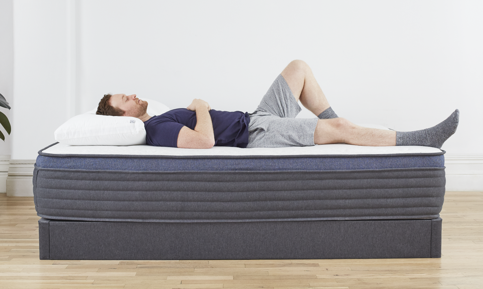 Man laying on his back on Helix Midnight Luxe mattress on Helix Foundation
