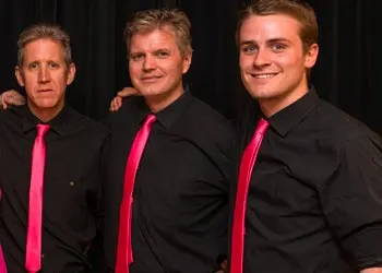 Three men wearing black dress shirts and fuchsia ties.