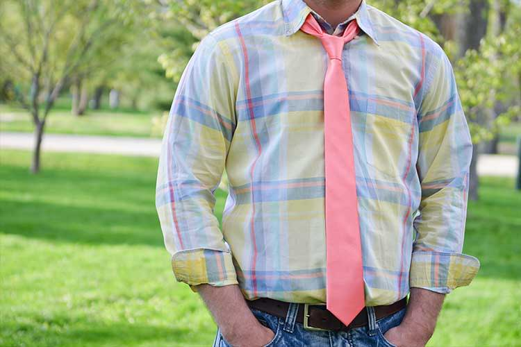 Man wearing a plaid shirt, jeans and coral skinny tie