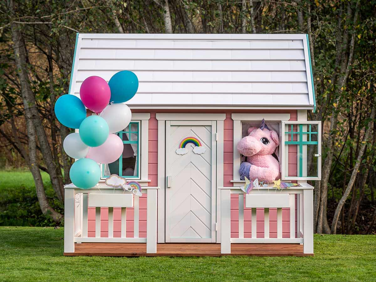 Pink wooden playhouse Unicorn with a white porch and decorations with forest background by WholeWoodPlayhouses