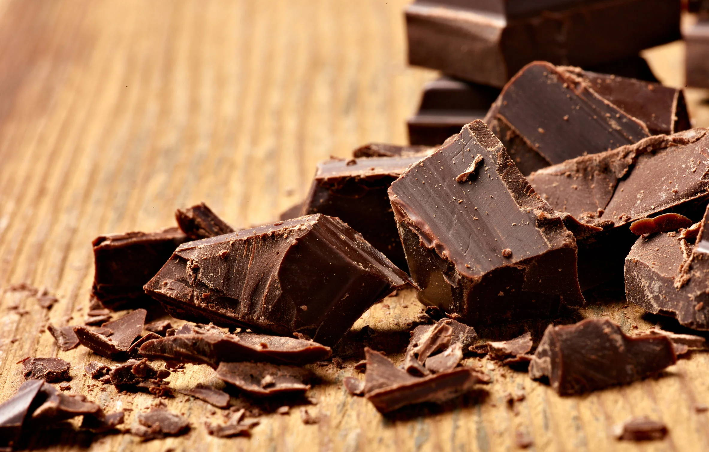 Chunks of chocolate broken up on a wooden slab