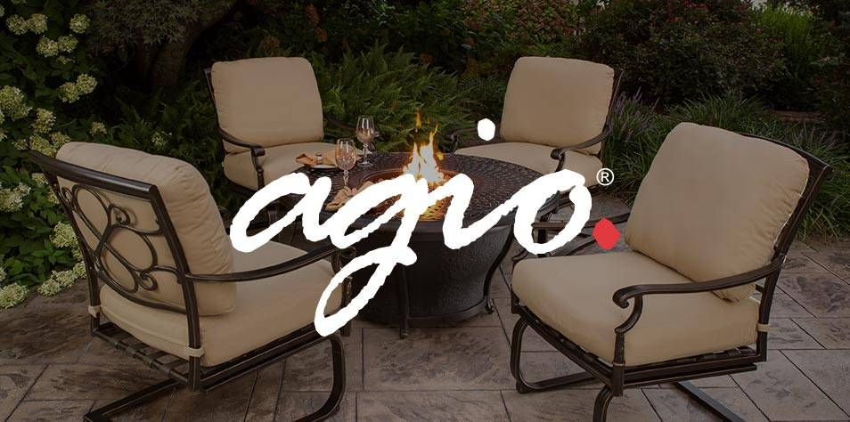 An Agio fire pit is ignited in a stunning backyard amidst 4 deep seated patio chairs.