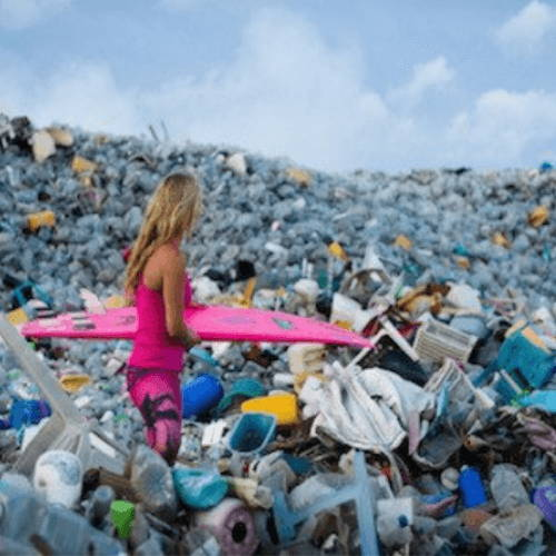 Woman Holding Surfboard in Ocean of Plastics
