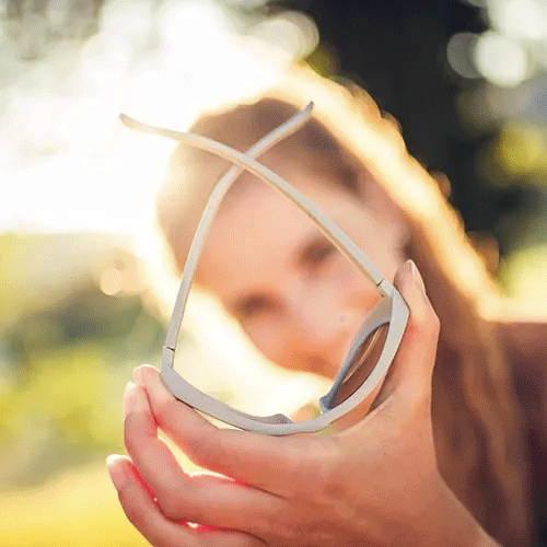 Frau hält Brille vor dem Gesicht