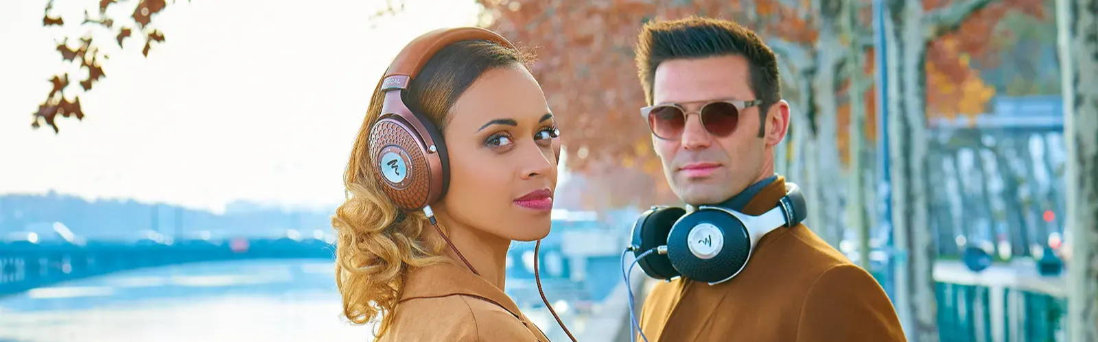 A well dressed woman and a gentleman posing with Focal Stellia and Focal Elegia closed back headphones.