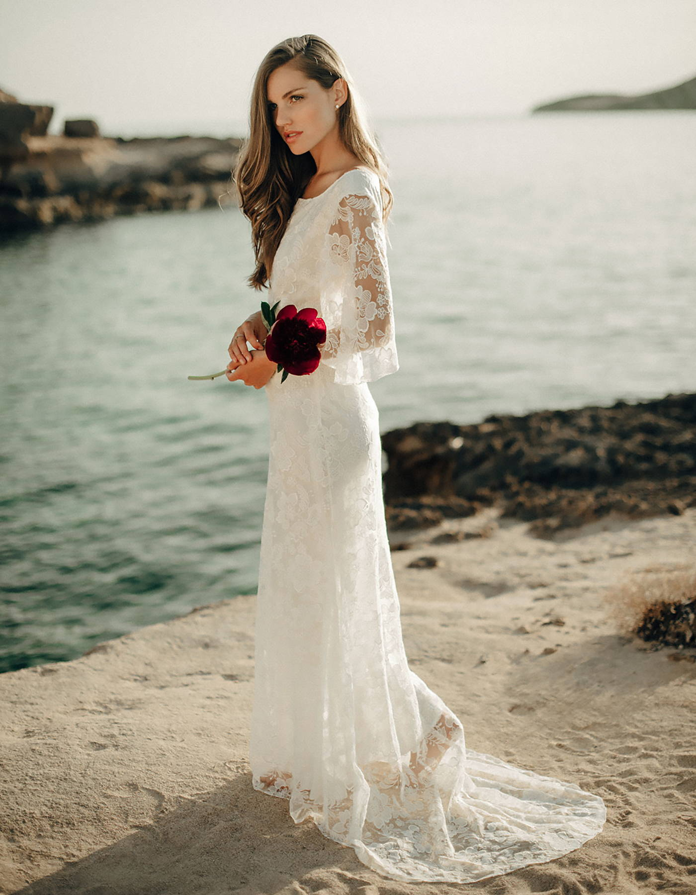 This vintage style lace wedding dress has sheer flutter sleeves and is the perfect boho wedding dress.