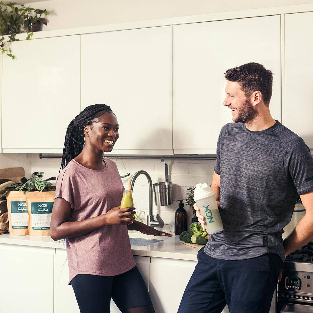 Black women and white man drinking NGX BodyFuel in a kitchen