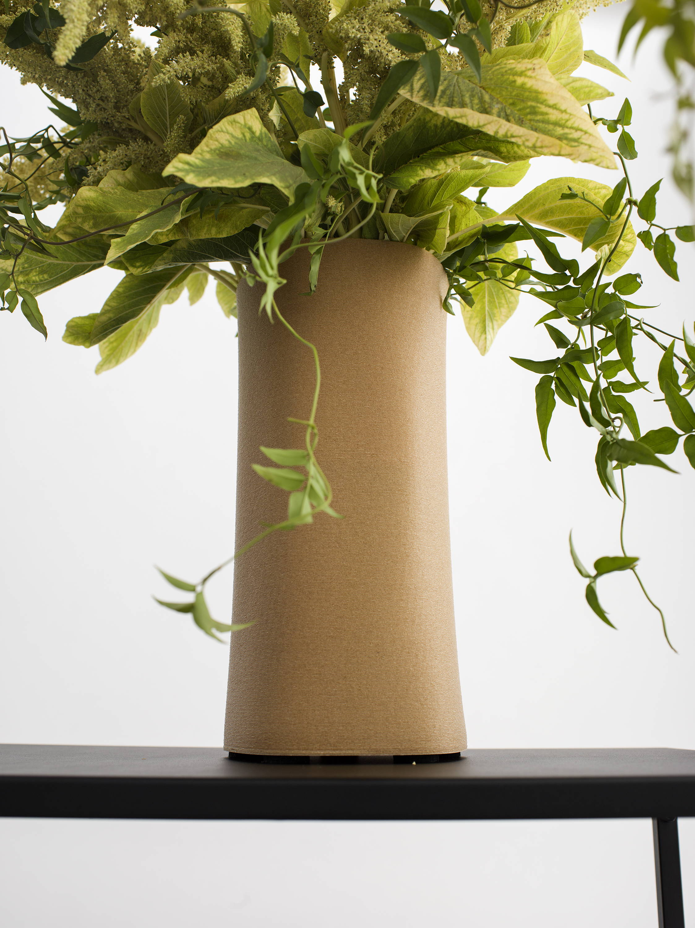 Tall custom vase with greenery made of 3D printed plant resin sitting on table