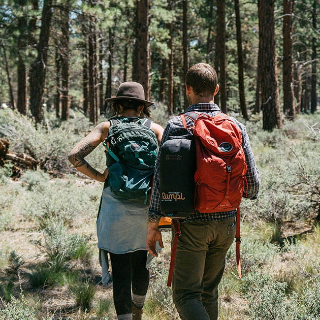A couple backpacking through the forest with a Rumpl blanket