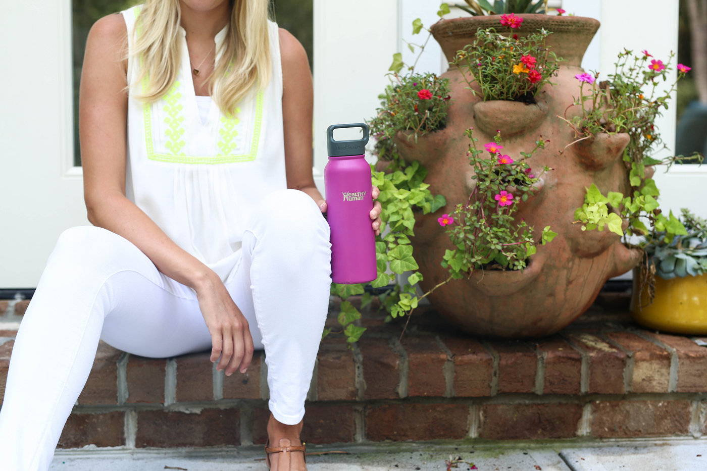 Woman holding a Healthy Human Stein water bottle next to a terra cotta planter