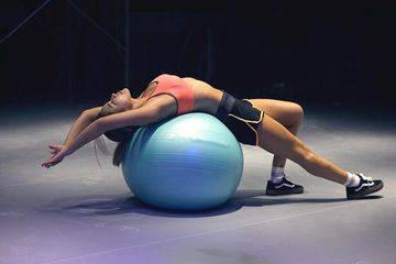 woman laying over a swiss ball