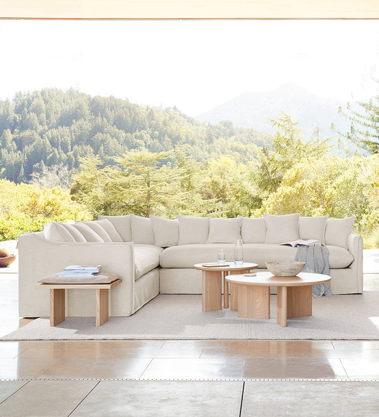 A living room furnished with a Reyes Stool and Morro Tables in a Natural Ash finish, a Hayes Chair in beech and Snow hair-on-hide, and a Dune sectional in Buff performance chenille.