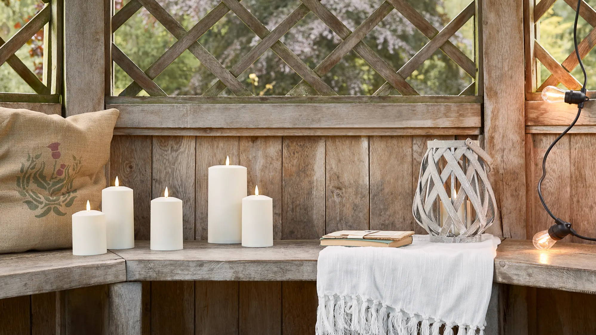Summerhouse with TruGlow candles, woven garden lantern and festoons displayed on bench