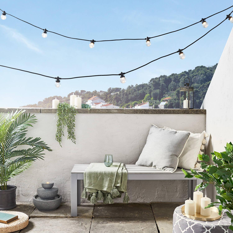 Über einem Balkon aufgespannte warmweiße Pro Connect Party Lichterkette mit schwarzem Kabel und transparenten Birnen
