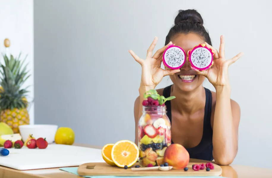 Woman smiling with a tropical fruit salad, being playful covering her eyes with dragon fruit|5 Ways To Boost Your Gut Health and Immune System |Gut Health and Your Immune System