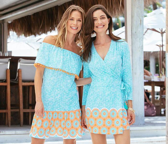 Two women wearing the Cabana Life Aqua Citrus Off The Shoulder Ruffle Dress & the Aqua Citrus Wrap Romper at a beach bar.