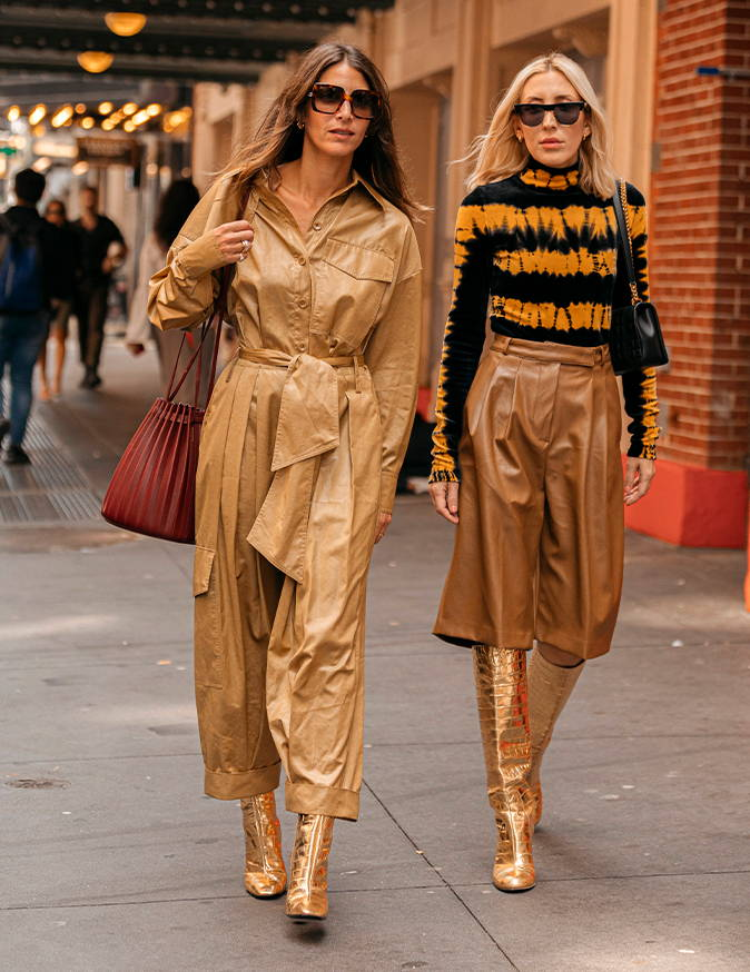 Two women walking down the street. Woman on the left is wearing camel liquid drape and sunglasses.