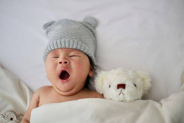 Baby Wearing A Grey Knit Hat Yawning