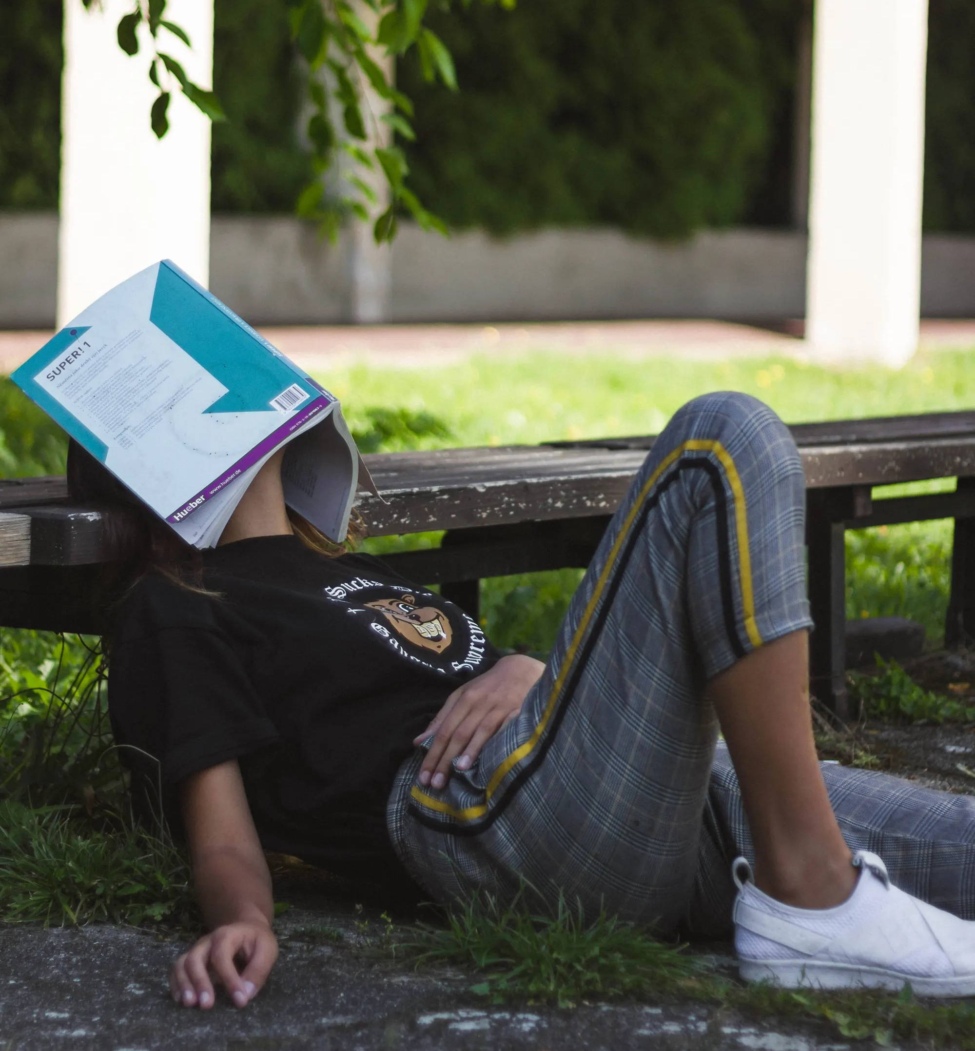 Woman sitting on the grass leaning on a bench with a book on her face, sleeping.