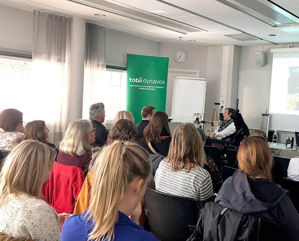 Publikum hört zu und macht Notizen während einer Veranstaltung vor Ort von Tobii Dynavox