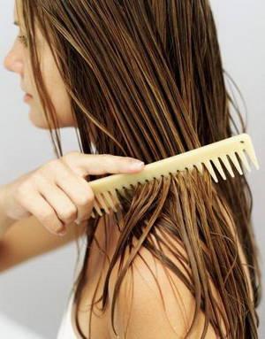 A woman runs a comb through damp hair