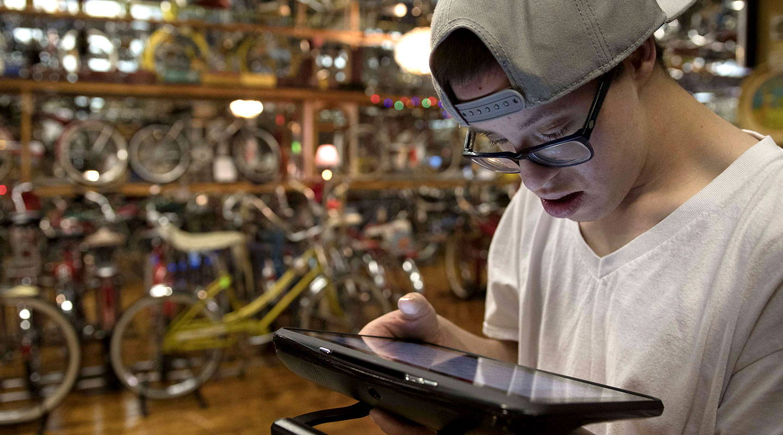 Junger Mann verwendet ein UK-Gerät von Tobii Dynavox
