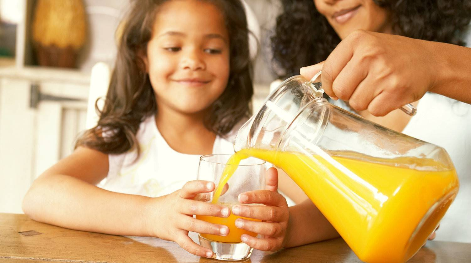 Featured | Mother pouring fresh orange juice from a jug  | Natural Vitamin C vs Synthetic Vitamin C: What's The Difference?