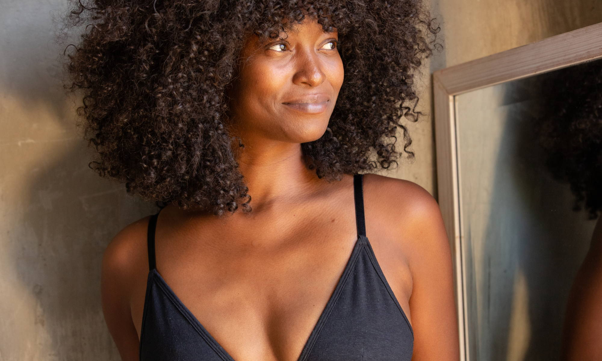 A woman wearing a black WAMA triangle bralette looks to the side, wondering how to get deodorant stains out of bras.