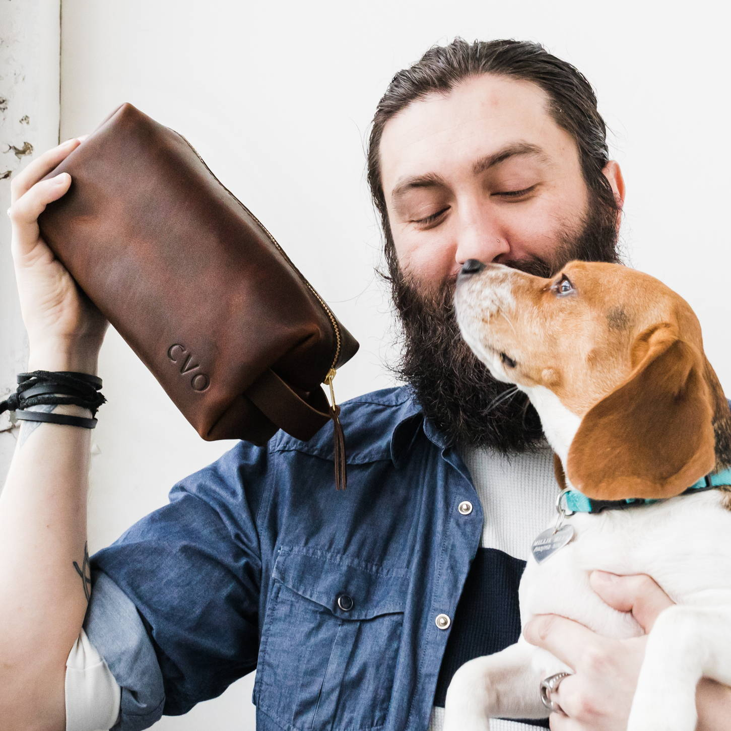 man holding cute dog and a grizzly leather dopp kit