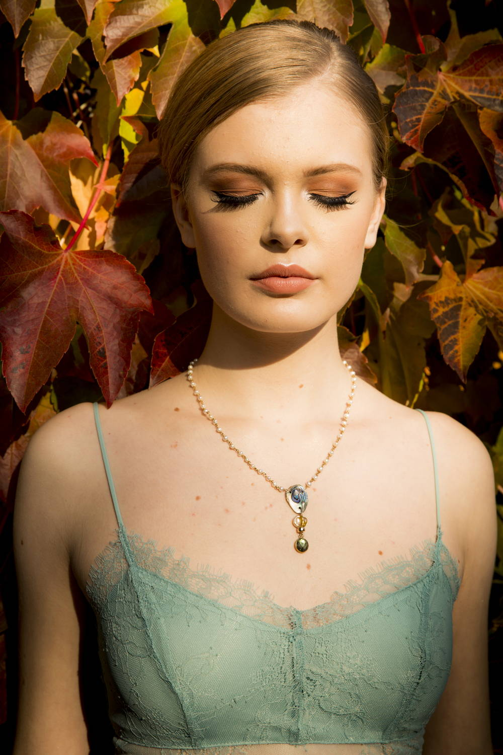 Siren Style Number Two: One of our sirens models The Burning Flame Pearl Necklace, a sparkly handmade designer pearl and gemstone siren necklace. A one-of-a-kind pendant featuring flashing labradorite, iridescent abalone shell and pearl hangs from a delicate white pearl chain.