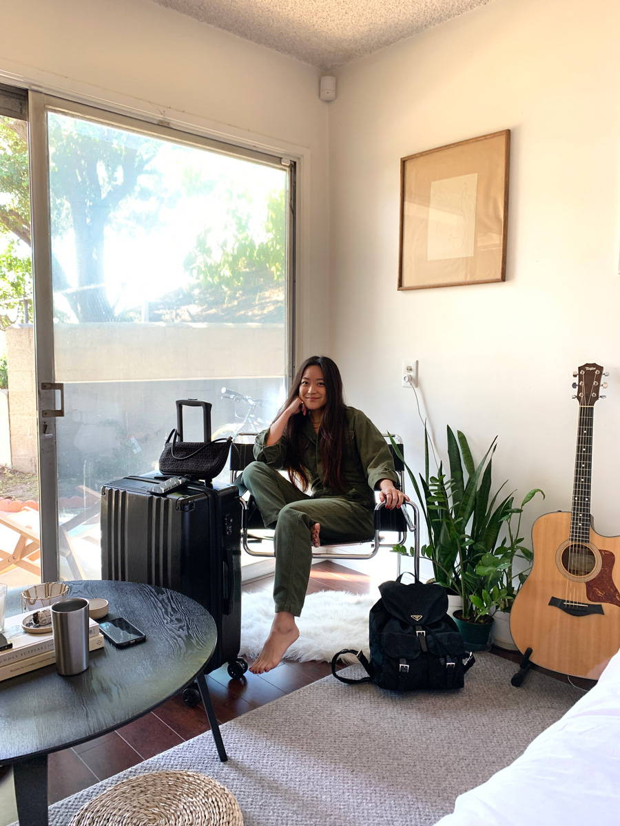 Alexa Yoshimoto in her Los Angeles home with her CALPAK Ambeur Medium luggage in black and Portable Charger in Midnight Marble.