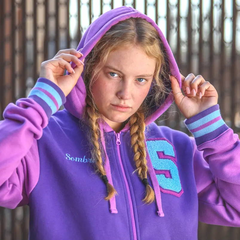 A model wearing the Overwatch Varsity Sombra Hoodie