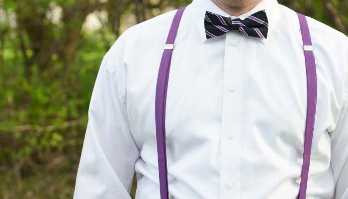 Man wearing purple skinny suspenders, a white shirt and black and purple striped bow tie outside