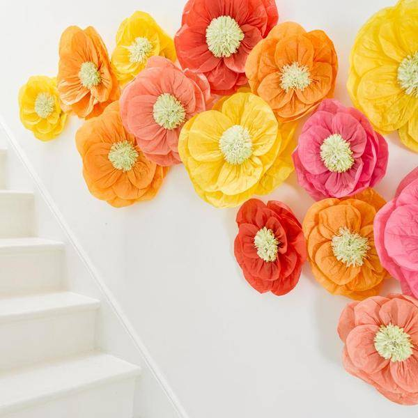 A photo of a white wall with vibrant, colourful flower decorations stuck onto it for a party display in a range of yellows, oranges, reds and pinks