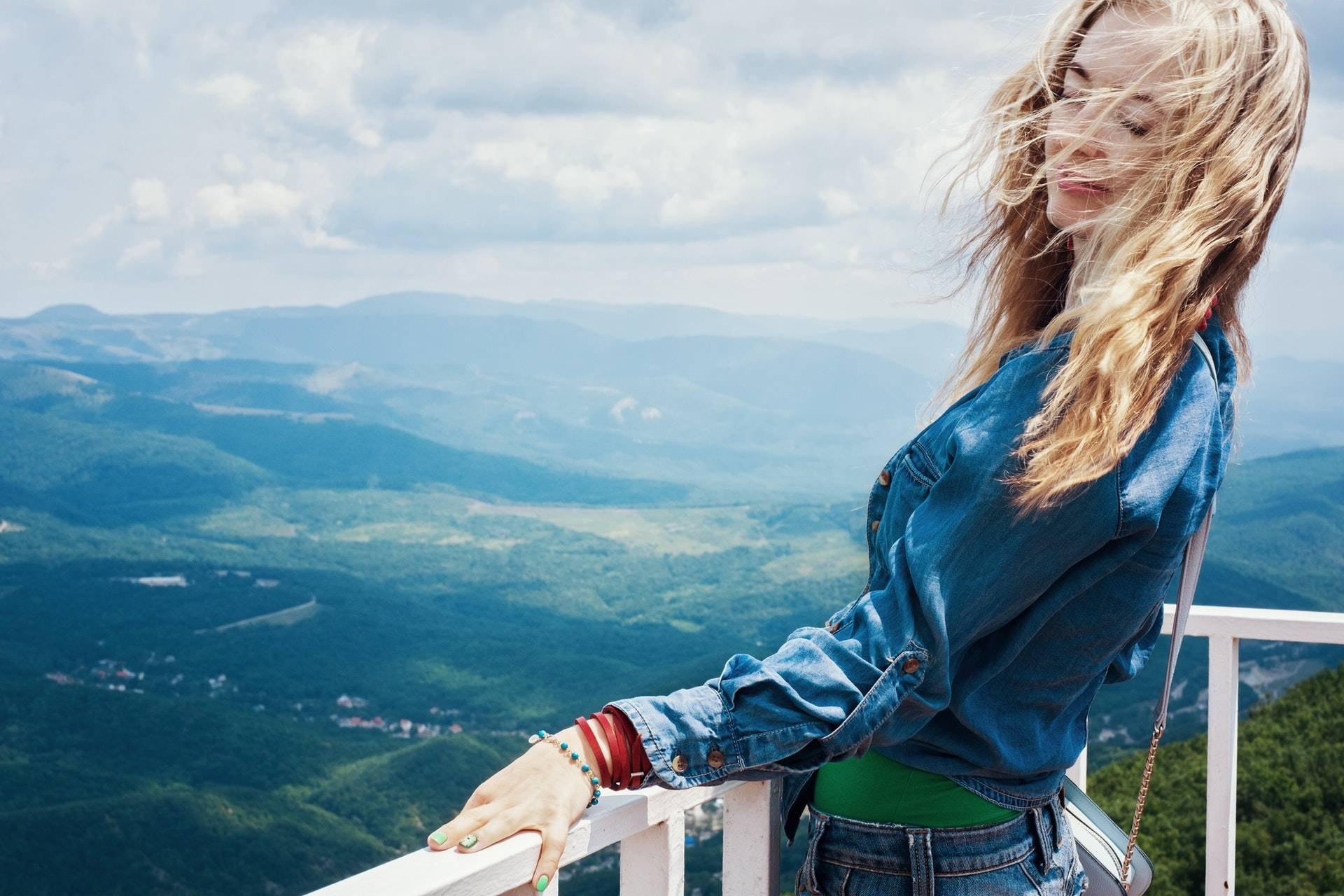 Woman leaning over railing with beautiful view