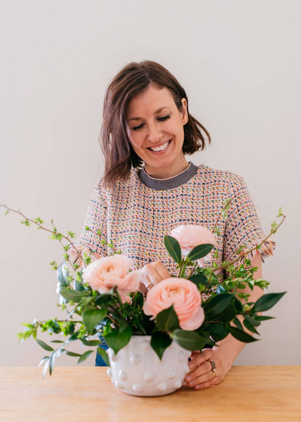Emily Hall of Threads and Blooms fills a vase with fresh spring blooms