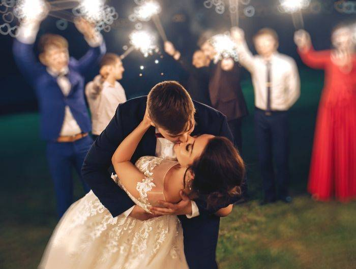 Bride and groom kissing outside at night