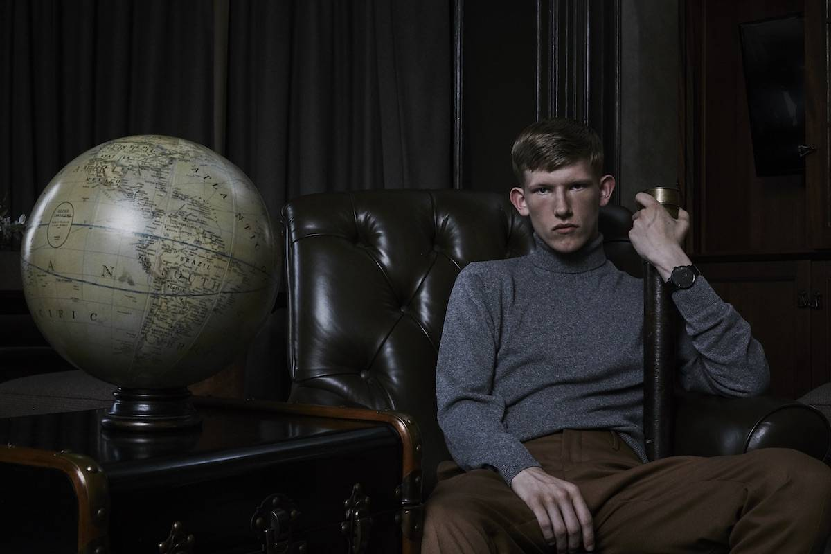 Scottish model Connor Newall in an antique leather chair with a globe and telescope for Kartel Scotland watches AW18 campaign
