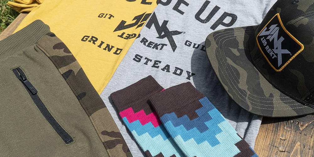 Photo showing a collection of JINX Brand products, including shirts, shirts, socks and a hat